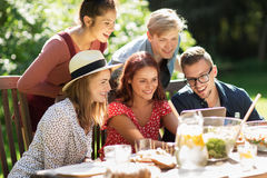 Les amis avec le PC de comprimé au dîner en été font du jardinage Photo stock