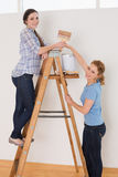 Les amis avec le pinceau et peuvent sur l'échelle dans une nouvelle maison Images stock