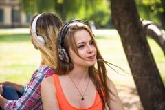 Les amis ayant l'amusement, écoutant la musique et détendent en parc Les adolescentes heureuses passent le temps dans la ville Image libre de droits