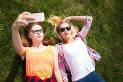 Les amis ayant l'amusement, écoutant la musique et détendent en parc Les adolescentes heureuses passent le temps dans la ville Images stock