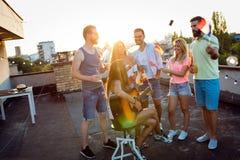 Les amis ayant l'amusement et buvant des cocktails extérieurs sur un dessus de toit se réunissent Photos stock