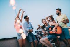 Les amis ayant l'amusement et buvant des cocktails extérieurs sur un dessus de toit se réunissent Image libre de droits