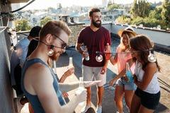 Les amis ayant l'amusement et buvant des cocktails extérieurs sur un dessus de toit se réunissent Images libres de droits