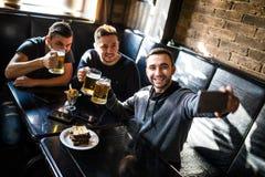 Les amis beaux boivent de la bière, font le selfie et sourient tout en se reposant dans le bar Temps de bière Images stock
