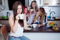 Les amis boivent du thé et du café à la cuisine, portrait de la jeune belle brune dans le premier plan, femme avec la tasse blanc Image libre de droits