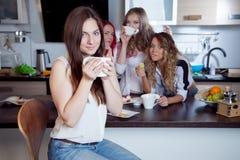 Les amis boivent du thé et du café à la cuisine, portrait de la jeune belle brune dans le premier plan, femme avec la tasse blanc Photographie stock