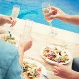 Les amis célèbrent à la partie par la piscine Image libre de droits