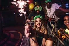 Les amis célèbrent le jour du ` s de StPatrick avec des cierges magiques la nuit Photographie stock