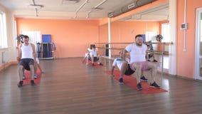 Les amis caucasiens beaux d'hommes s'exercent dans un gymnase moderne dans une formation de vapeur de groupe pour la résistance e banque de vidéos