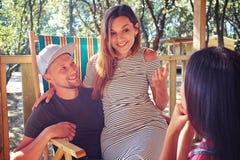 Les amis causent tout en se reposant sur des chaises de plage d'été à un r Photo stock