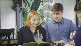 Les amis choisissent dans le menu ce qu'à passer commande dans un restaurant banque de vidéos