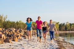 Les amis courent le long du bord de la mer, tenant des mains et le laughi Photos libres de droits