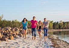 Les amis courent le long du bord de la mer, tenant des mains et le laughi Image stock