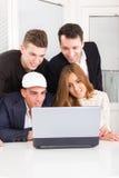 Les amis curieux regardant l'ordinateur portable surveillent ensemble Images libres de droits