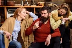 Les amis dépensent des loisirs dans l'intérieur confortable Homme et dames sur les visages heureux discutant et buvant du vin cha Images stock