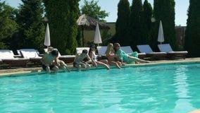 Les amis détendant par la piscine et un type saute dans l'eau obtenant tout le monde humide clips vidéos