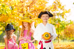 Les amis dans des costumes de Halloween tiennent le petit potiron Images stock