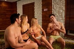 Les amis dans des maillots de bain rient du jacuzzi au centre de station thermale Photo libre de droits