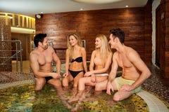 Les amis dans des maillots de bain rient du jacuzzi au centre de station thermale Images stock