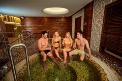 Les amis dans des maillots de bain rient du jacuzzi au centre de station thermale Photos libres de droits
