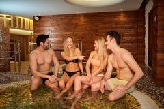 Les amis dans des maillots de bain rient du jacuzzi au centre de station thermale Photographie stock libre de droits