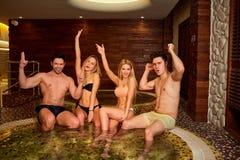 Les amis dans des maillots de bain rient du jacuzzi au centre de station thermale Images libres de droits
