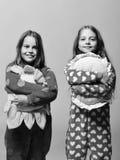 Les amis dans la polka rose ont pointillé des pyjamas d'isolement sur le fond rose Les enfants avec les visages heureux tiennent  Photographie stock