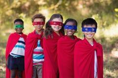 Les amis dans le super héros rouge costume la position au terrain de camping Photos libres de droits