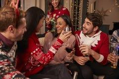 Les amis dans les pullovers de fête célèbrent à la fête de Noël Photographie stock libre de droits