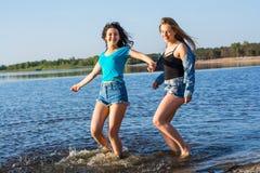Les amis dansent et éclaboussent l'eau sur un bord de la mer, riant Images stock