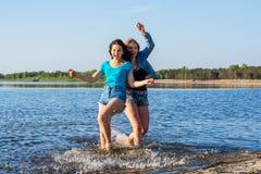 Les amis dansent et éclaboussent l'eau sur un bord de la mer, riant Photos stock