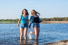 Les amis dansent et éclaboussent l'eau sur un bord de la mer, riant La TW Photographie stock libre de droits