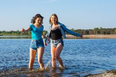 Les amis dansent et éclaboussent l'eau sur un bord de la mer, riant Yo Photographie stock libre de droits