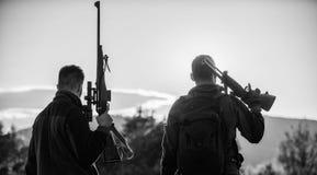 Les amis de chasseurs appr?cient des loisirs Les garde-chasse d'amis de chasseurs avec des armes ? feu silhouettent le fond de ci photos stock
