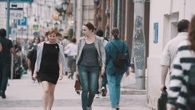 Les amis de femmes marchant avec des personnes se serrent sur des rues de ville clips vidéos