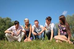 Les amis de groupe s'asseyent sur l'herbe Photo libre de droits