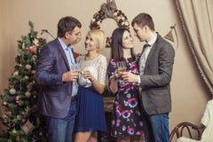 Les amis de quatre hommes et femmes avec le bacale célèbrent avec le champag Photographie stock