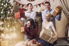 Les amis de quatre hommes et femmes donnent des cadeaux dans l'interi de Noël Photographie stock libre de droits