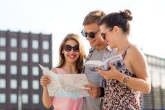 Les amis de sourire avec la carte et la ville guident dehors Photographie stock libre de droits