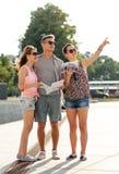 Les amis de sourire avec la carte et la ville guident dehors Photos libres de droits