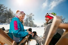 Les amis de sourire détendent dans les chaises sur le dessus de montagne Vue arrière Photos libres de droits