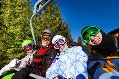 Les amis de sourire dans des masques de ski s'asseyent sur l'ascenseur Image stock