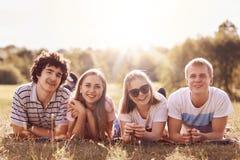 Les amis de sourire ont des expressions heureuses, se trouvent sur le plaid sur la terre, se réjouissent le jour ensoleillé, rega Photos stock