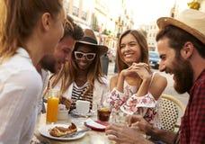 Les amis des vacances ayant l'amusement en dehors d'un café dans Ibiza, se ferment  Photographie stock