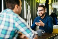 Les amis discutent boire du café dans un café Photos stock