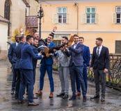 Les amis du ` s de marié le tiennent devant l'église dans la petite place Ville de Sibiu en Roumanie Images stock