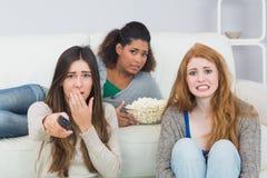 Les amis effrayés avec à télécommande et le maïs éclaté roulent à la maison Photos stock