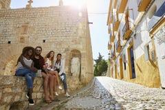 Les amis en vacances dans Ibiza s'asseyent sur un mur regardant à l'appareil-photo Photo stock