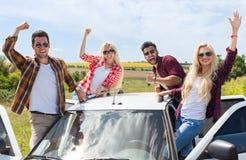 Les amis enthousiastes sur les personnes extérieures de bras d'augmenter de campagne de toit de voiture sourient Image stock
