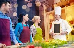 Les amis et le chef heureux font cuire avec le menu dans la cuisine Photo libre de droits
